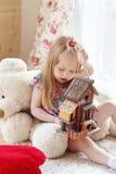 La bambina bionda graziosa si siede su tappeto vicino alla finestra Immagini Stock