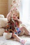 La bambina bionda graziosa si siede su tappeto vicino alla finestra Fotografia Stock Libera da Diritti