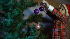 La bambina in cappuccio rosso di Santa orna l'albero di Natale video d archivio