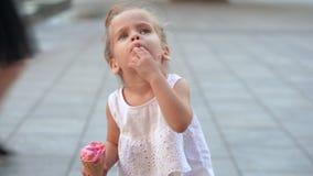 La bambina caucasica sveglia gode del gelato in un cono della cialda che cammina nel parco Il bambino mangia il gelato luminoso stock footage
