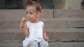 La bambina caucasica sveglia gode del gelato in un cono della cialda che cammina nel parco Il bambino mangia il gelato luminoso archivi video