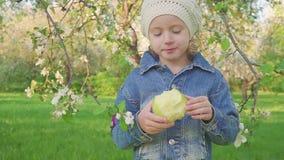 La bambina che mangia la mela verde sulla fioritura fa il giardinaggio archivi video