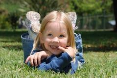 La bambina che pone su un'erba Fotografia Stock
