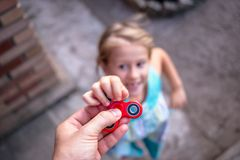 La bambina che salta alla mano con un filatore fotografie stock