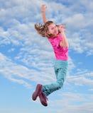La bambina che salta e che balla contro il cielo nuvoloso blu Fotografia Stock