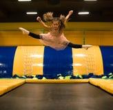 La bambina che salta su un trampolino e che fa per attorcigliare la spaccatura nella stanza del gioco per i bambini fotografia stock libera da diritti