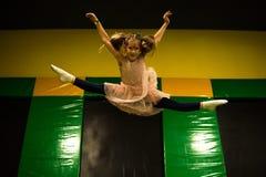 La bambina che salta su un trampolino e che fa per attorcigliare la spaccatura nella stanza del gioco per i bambini fotografia stock