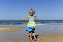 La bambina che salta sulla spiaggia Fotografia Stock