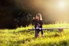 La bambina che si siede su un banco di legno soffia le bolle nei raggi Fotografia Stock Libera da Diritti
