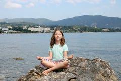 La bambina che si siede su una roccia e medita Fotografia Stock