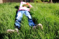La bambina che si trova sull'erba Immagini Stock