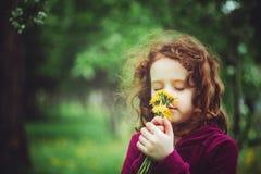 La bambina chiusa lei occhi e respira i denti di leone gialli in Th fotografie stock libere da diritti