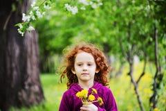 La bambina chiusa lei occhi e respira i denti di leone gialli in Th fotografia stock