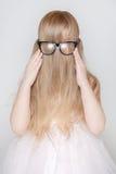 La bambina con capelli lunghi ha coperto il suo fronte Fotografie Stock Libere da Diritti