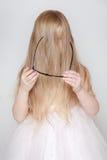 La bambina con capelli lunghi ha coperto il suo fronte Fotografia Stock Libera da Diritti