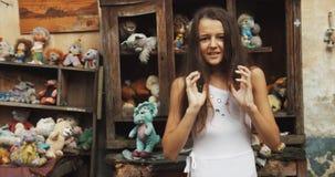 La bambina con capelli lunghi scuri hsouting nel giardino in pieno dei giocattoli e di vecchia mobilia metraggio 4k Ritratto del  video d archivio