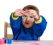 La bambina esamina le mani di colore Immagine Stock