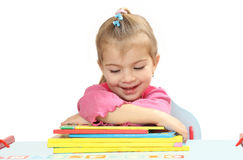 La bambina con i libri ad una tavola Fotografia Stock