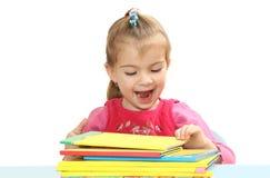 La bambina con i libri ad una tavola Immagine Stock