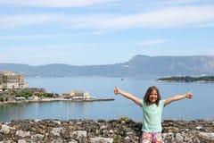 La bambina con i pollici aumenta la città Grecia di Corfù Fotografia Stock