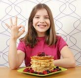 La bambina con il dessert dei panckaces e la mano giusta firmano Immagine Stock