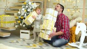 La bambina con il padre si diverte con i contenitori di regalo vicino all'albero di Natale a casa stock footage