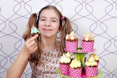 La bambina con impiastra il fronte ed i muffin Fotografia Stock