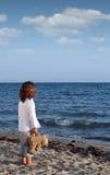 La bambina con l'orsacchiotto riguarda la spiaggia Fotografia Stock