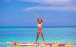 La bambina con la lecca-lecca si diverte sul surf dentro immagini stock libere da diritti