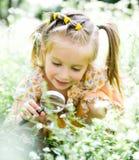 La bambina con la lente d'ingrandimento esamina il fiore Fotografia Stock