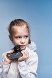 La bambina con la macchina fotografica distoglie lo sguardo Immagini Stock Libere da Diritti