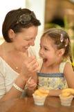 La bambina con la madre mangia Fotografie Stock