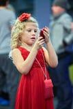 La bambina con la rosa rossa in capelli esamina il telefono cellulare Immagini Stock Libere da Diritti