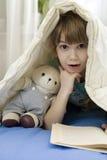 La bambina con riguarda il sofà Fotografia Stock Libera da Diritti