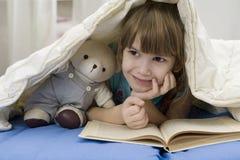 La bambina con riguarda il sofà Fotografia Stock