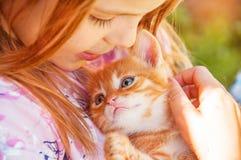 La bambina con un gattino rosso in mani si chiude su BESTFRIENDS I fotografie stock