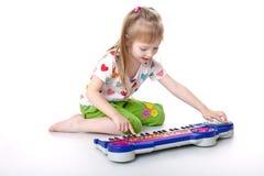 La bambina con un giocattolo musicale Immagine Stock