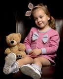 La bambina con un orsacchiotto riguarda un fondo nero fotografie stock libere da diritti