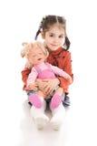 La bambina con una bambola isolata su un bianco Fotografia Stock Libera da Diritti