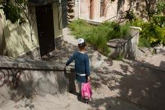 La bambina con uno zaino della scuola scende le scale Immagini Stock Libere da Diritti