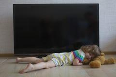 La bambina concettuale del ritratto sta dormendo sul pavimento sui precedenti di uno schermo nero della TV Fotografia Stock