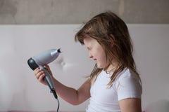 La bambina del bambino asciuga i capelli, prendenti la cura voi stesso, Th immagine stock libera da diritti