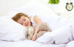 La bambina del bambino dorme nel letto con l'orsacchiotto immagini stock