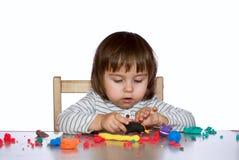 La bambina del ritratto sta giocando con pasta coloful Fotografia Stock