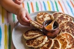 La bambina della prima colazione di mattina tira una mano verso un piatto con il chee immagini stock libere da diritti
