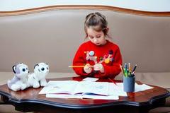 La bambina di pensil di natale del nuovo anno scrive a lettera Santa il sofà rosso della tavola del bambino della penna del gioca Fotografia Stock Libera da Diritti