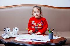 La bambina di pensil di natale del nuovo anno scrive a lettera Santa il sofà rosso della tavola del bambino della penna del gioca Immagini Stock Libere da Diritti