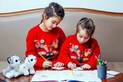 La bambina di pensil di natale del nuovo anno scrive a lettera Santa il sofà rosso della tavola del bambino della penna del gioca Immagine Stock