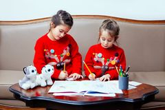 La bambina di pensil di natale del nuovo anno scrive a lettera Santa il sofà rosso della tavola del bambino della penna del gioca Immagini Stock