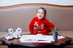 La bambina di pensil di natale del nuovo anno scrive a lettera Santa il sofà rosso della tavola del bambino della penna del gioca Fotografie Stock Libere da Diritti